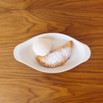 Handmade Fried Pie $5Seasonal Fruit Filling, Topped with Powdered Sugar. With a Scoop of Vanilla Ice Cream, add $3.